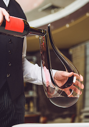 A waiter pours red wine into a large swan decanter